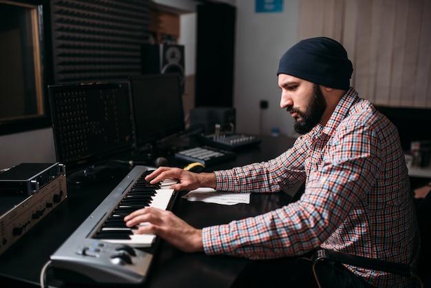 Audio engineering, geluidsman werkt met synthesizer in studio. professionele digitale geluidsopnametechnologie Premium Foto