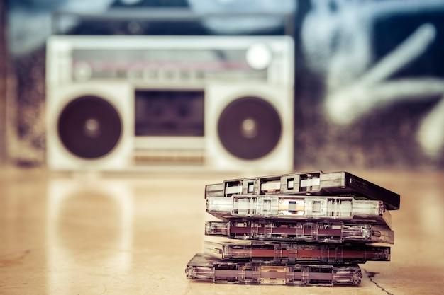 Audiocassettes gestapeld en op de grond geplaatst met een oude boombox Premium Foto