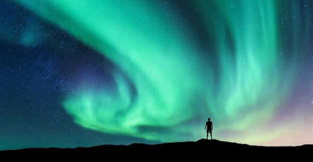 Aurora borealis en silhouet van de staande man Premium Foto