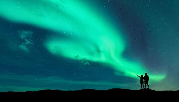Aurora borealis en silhouet van staande man en vrouw die naar het noorderlicht wijzen Premium Foto