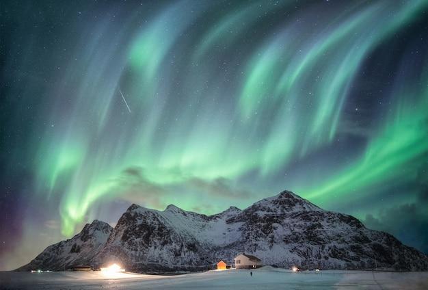 Aurora borealis met sterrenhemel over sneeuwbergketen met verlichtingshuis in flakstad Premium Foto