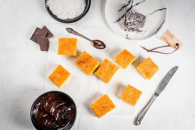 Australische keuken. bereiding van traditioneel australisch dessert lamington: koekje in chocolade met kokosscheerpoeder. bovenaanzicht witte tafel. Premium Foto