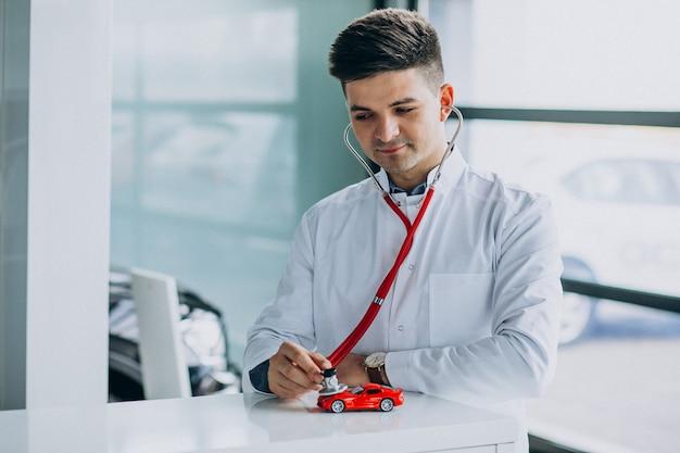 Auto arts met een stethoscoop in een autotoonzaal Gratis Foto