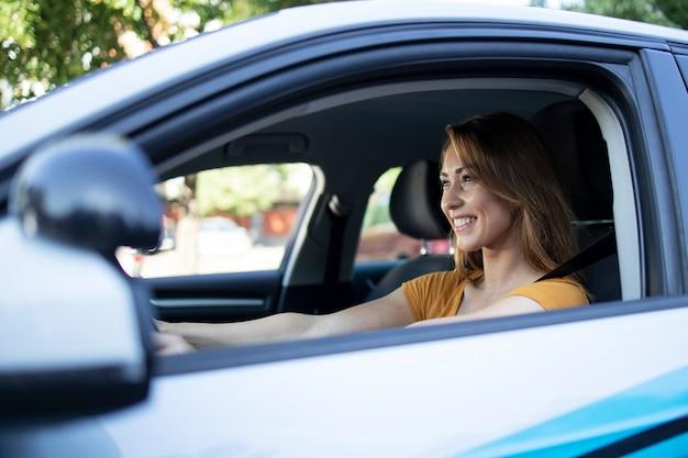 Auto binnenaanzicht van vrouwelijke bestuurder geniet van autorijden Gratis Foto