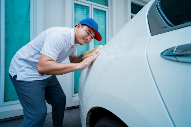 Auto detaillering, man in blauwe uniform schoon een witte auto in de hand met een microfiber wassen grote auto. Premium Foto