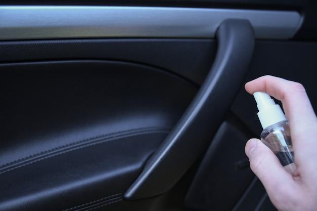 Auto-interieur reinigen en besproeien met desinfectievloeistof. desinfectie van het stuur en de handvatten van de auto. coronavirus bescherming. virusbescherming. desinfecterend voertuig binnenin Premium Foto