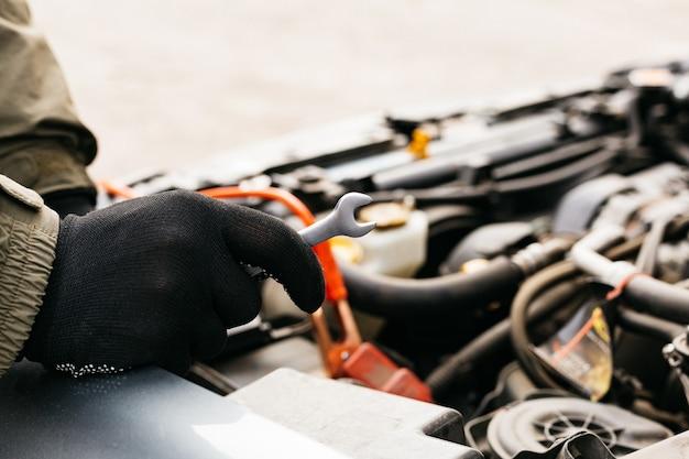 Auto monteur ingenieur met behulp van een moersleutel tijdens de vaststelling van een auto Premium Foto