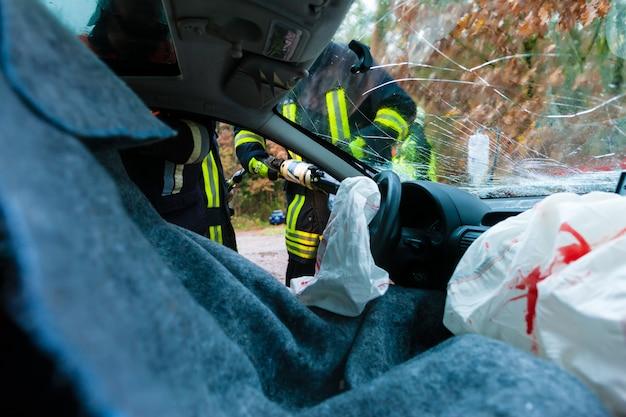 Auto-ongeluk, slachtoffers in gecrasht voertuig ontvangen eerste hulp Premium Foto