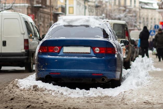Auto's geparkeerd aan een kant van de straat in de stad bedekt met vuile sneeuw in de winter. Premium Foto