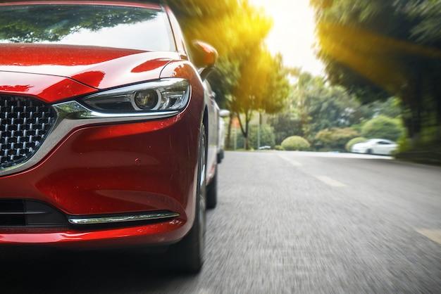 Auto's passeren het bos van asfaltweg Premium Foto