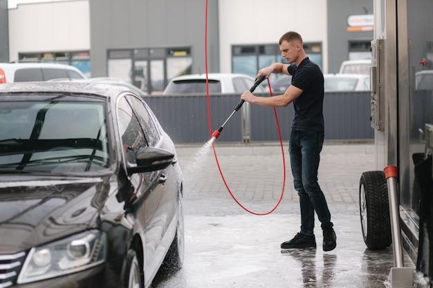 Auto schoonmaken met actief schuim. man zijn auto wassen op zelf autowassen. Premium Foto