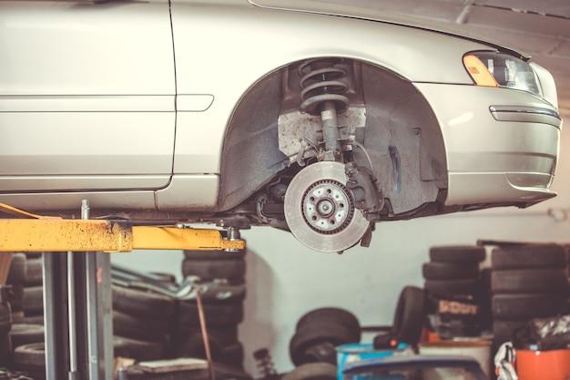 Auto servicecentrum concept, voertuig opgeheven op lift bij onderhoudsstation, auto reparatie en controle, reparatie van de auto Premium Foto