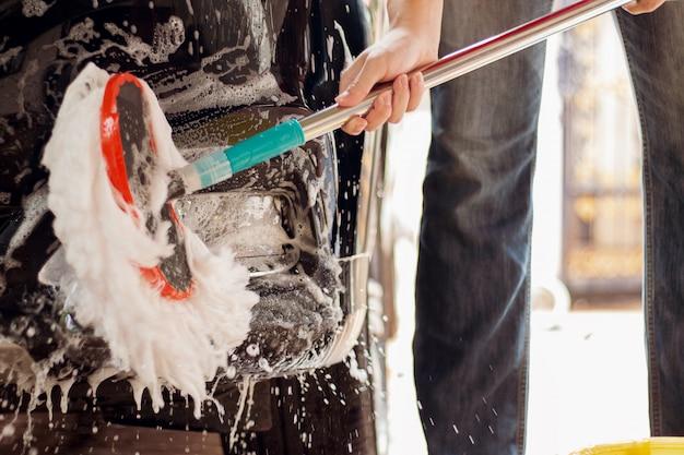 Auto wassen, auto reinigen spons gebruiken voor het wassen van auto Premium Foto