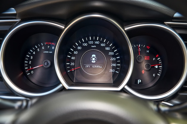 Autodashboard met rode achtergrondverlichting: kilometerteller, snelheidsmeter, toerenteller, brandstofniveau, watertemperatuur en meer. Premium Foto