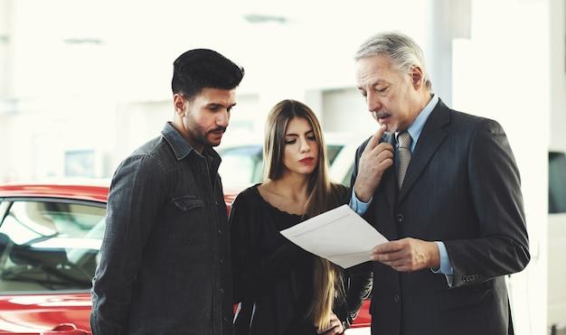 Autohandelaar die een contract aan een paar in een autoshowroom lezen Premium Foto