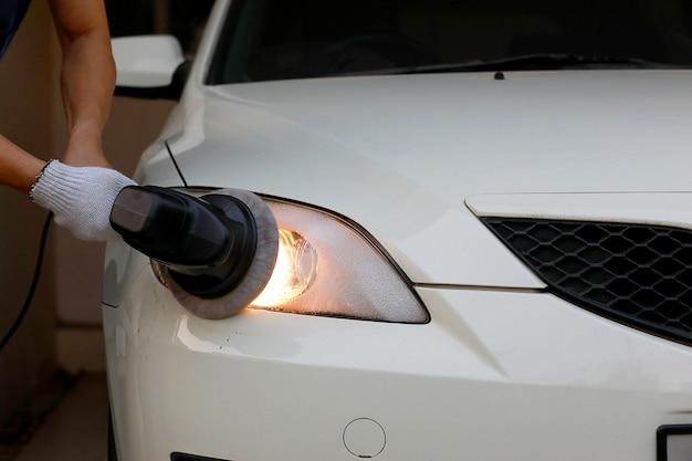 Autokoplampreiniging met elektrische polijstmachine met de hand van de arbeider. Premium Foto