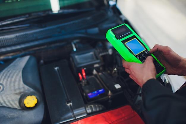 Automonteur controleert de motor en houdt de batterijmeter vast. Premium Foto