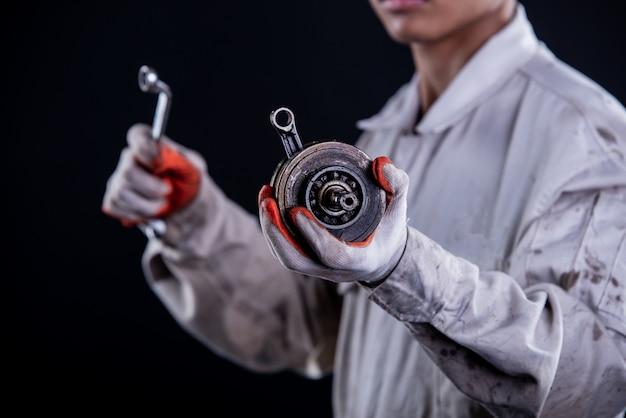 Automonteur dragen een witte uniforme stand houden moersleutel Gratis Foto