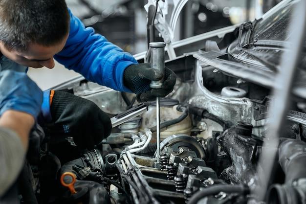 Automonteur in blauwe uniform vervangende gloeibougies in motor Premium Foto