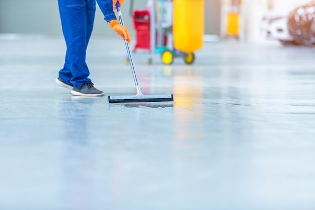 Automonteur repareren servicecentrum reinigen met dweilen om water van de epoxyvloer te rollen. in het autoreparatieservicecentrum. Premium Foto