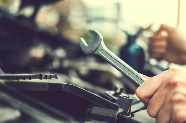 Automonteur werken in garage technicus handen van automonteur werken in auto reparatie service en onderhoud auto controleren. Premium Foto