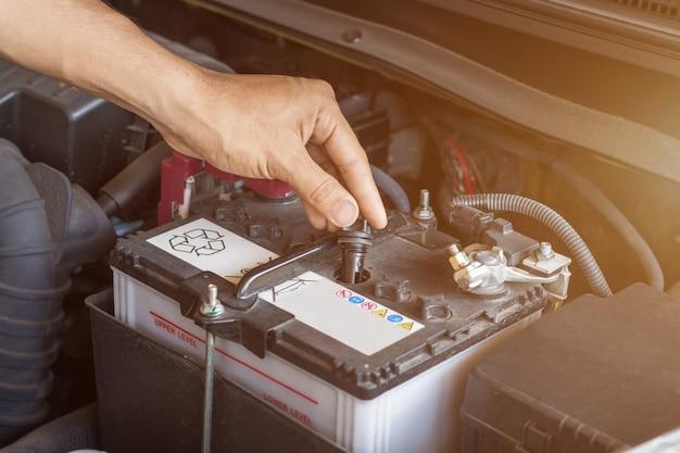 Automonteur werkt controleren systeemwater en batterij vullen een oude motor van een auto bij tankstation, vervangen en repareren voor rijden Premium Foto