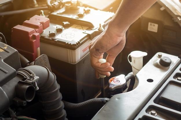 Automonteur werkt systeemwater controleren en een oude automotor vullen bij servicestation, vervangen en repareren voordat u gaat rijden Premium Foto