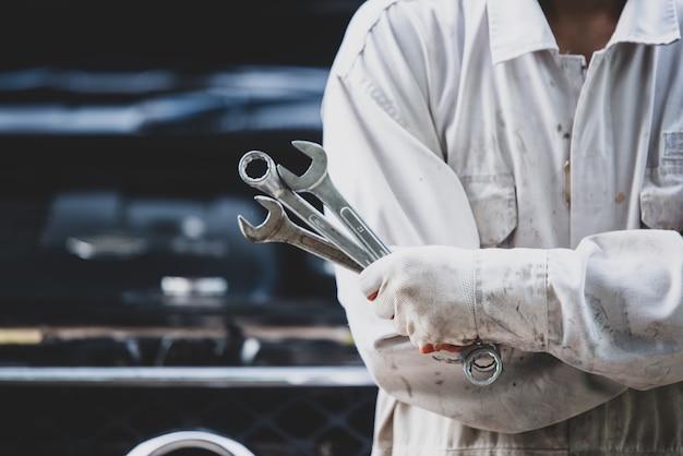 Autoreparateur die een witte uniform draagt en een moersleutel vasthoudt die een essentieel hulpmiddel is voor een monteur Gratis Foto