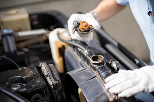 Autoreparatiemens die het koelmiddelsysteem, keteltank, in de oude auto controleren. Premium Foto