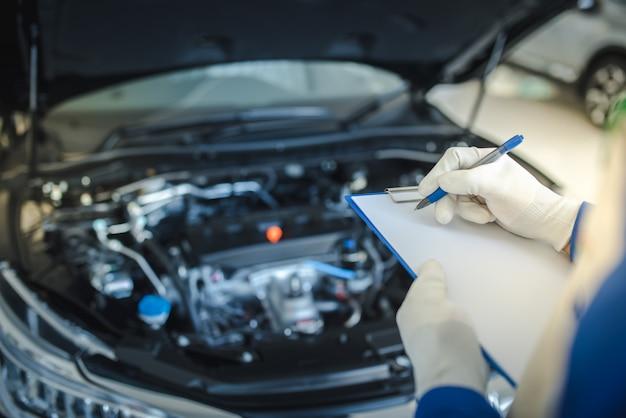 Autoservice, reparatie, onderhoudsconcept - aziatische automonteur man of smith schrijven naar het klembord in werkplaats of magazijn, technicus doet de checklist voor reparatiemachine voor een nieuwe auto Premium Foto