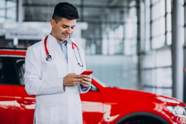 Autotechnicus met stethoscoop in een autotoonzaal praten aan de telefoon Gratis Foto
