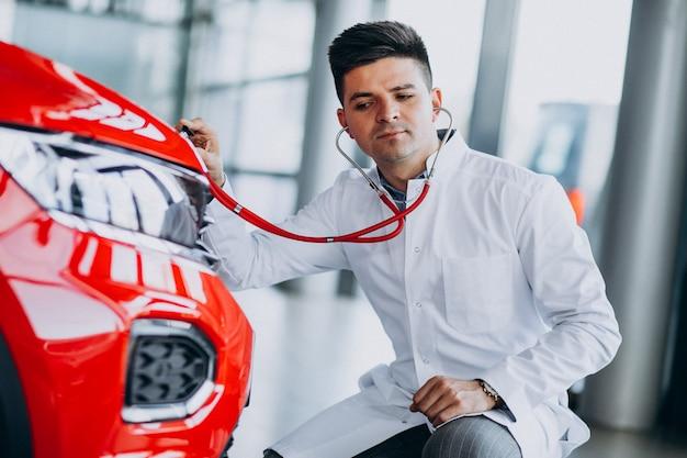 Autotechnicus met stethoscoop in een autotoonzaal Gratis Foto