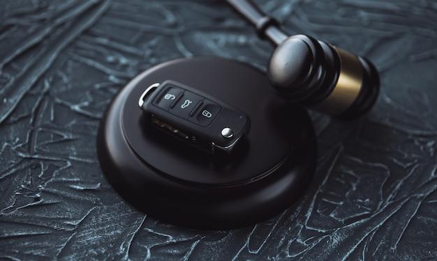 Autoveiling concept - hamer en autosleutel op het houten bureau Premium Foto