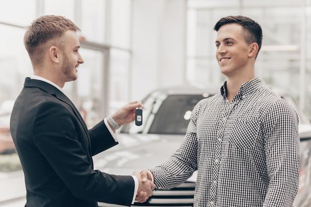 Autoverkoper die met een klant bij de dealer werkt Premium Foto