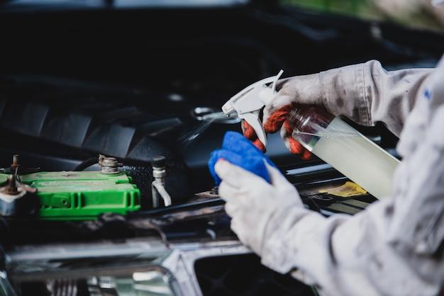 Autowasserettearbeider die een witte eenvormig dragen die zich een spons bevinden om de auto in het autowasserettecentrum schoon te maken, concept voor de autozorgindustrie. Gratis Foto