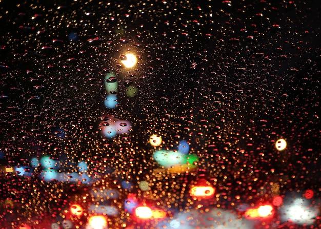 Autowindschermhoogtepunt van regendruppels met onscherpe opstopping op de stedelijke straat bij nacht Premium Foto