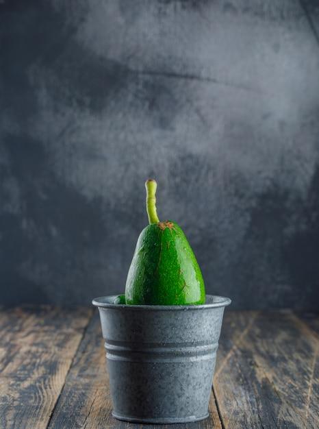 Avocado in een mini-emmer op houten en gips muur. zijaanzicht. Gratis Foto