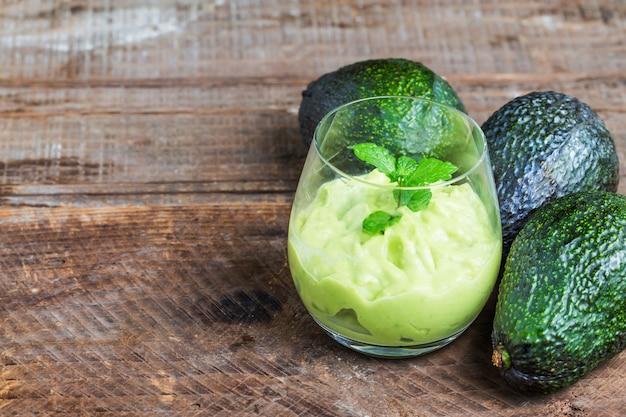 Avocado op een donkere houten achtergrond Gratis Foto
