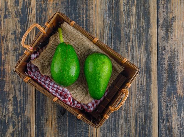 Avocado's in een mand op een houten tafel. plat lag. Gratis Foto