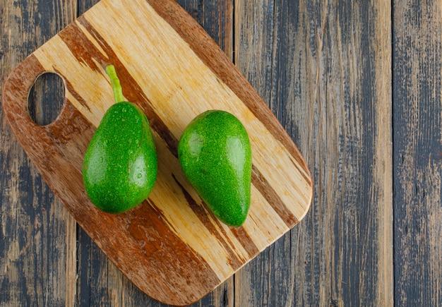 Avocado's op houten en snijplank. plat lag. Gratis Foto