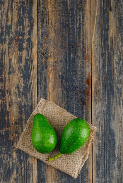 Avocado's op houten en stuk zak. bovenaanzicht. Gratis Foto