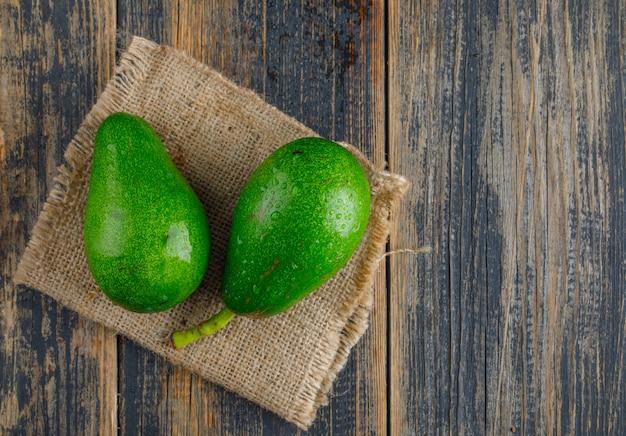 Avocado's op houten en stuk zak. plat lag. Gratis Foto