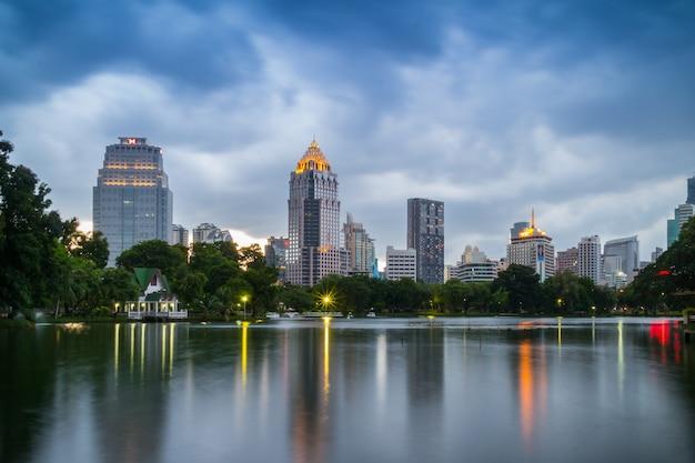 Avondscène van de skyline van bangkok in lumphini park Premium Foto