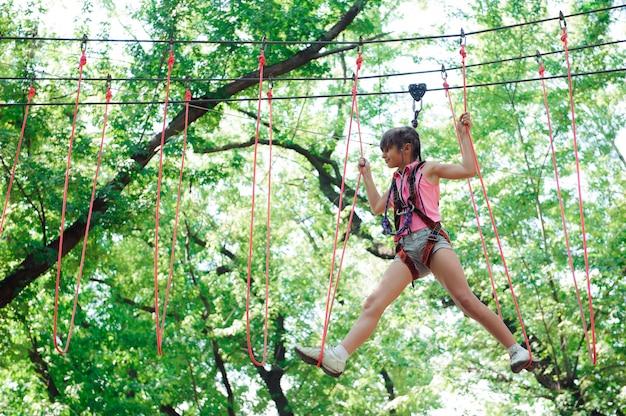 Avontuur klimmen high wire park - wandelen in het touw park meisje Premium Foto
