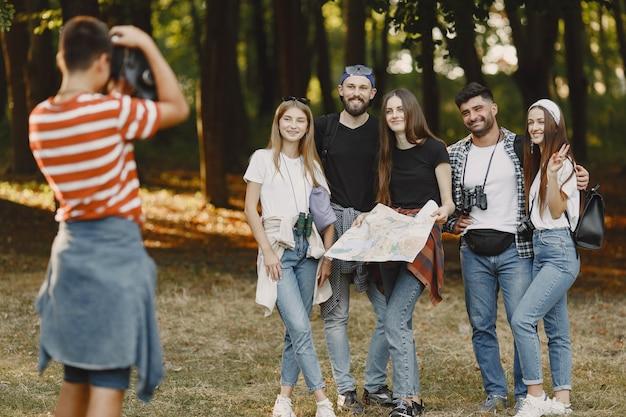 Avontuur, wandeling en mensenconcept. groep lachende vrienden in een bos. guy neemt een foto. Gratis Foto