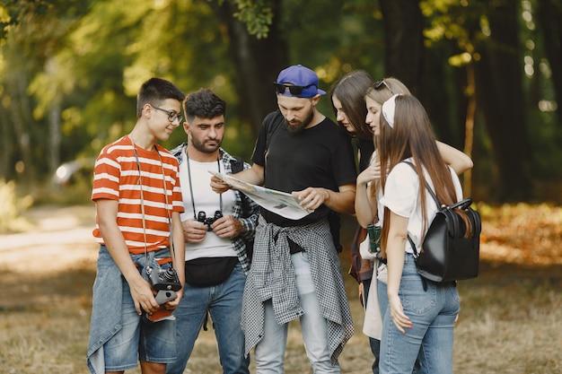 Avontuur, wandeling en mensenconcept. groep lachende vrienden in een bos. man met een kaart. Gratis Foto