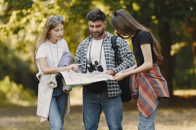 Avontuur, wandeling en mensenconcept. groep lachende vrienden in een bos. man met verrekijker. Gratis Foto