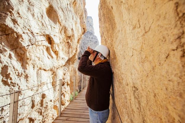 Avontuurlijke man van middelbare leeftijd met helm met verrekijker op haar vakantie op een bergexpeditie Premium Foto