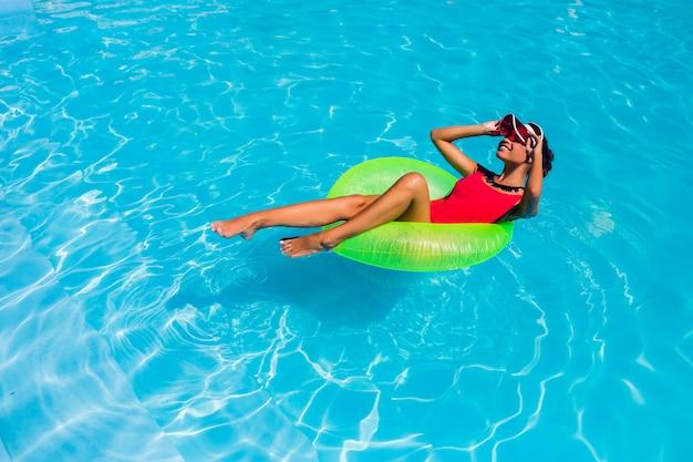 Awesome tan mooie jonge vrouw in bikini zwemmen in het zwembad en ontspannen in stijlvolle badkleding. Gratis Foto