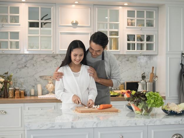 Aziaat die het zwangere paar koken thuis samen in de keuken verwachten Premium Foto